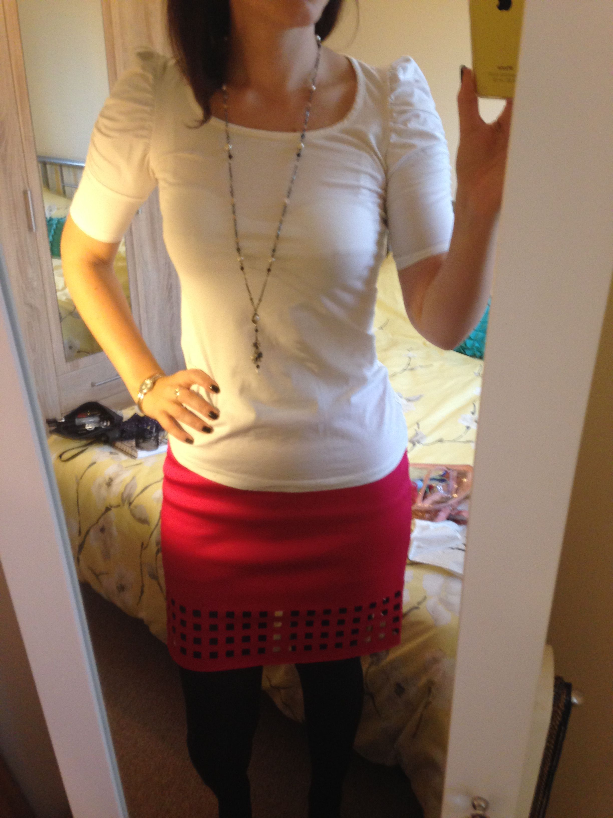 Bright pink skirt with square details, white top, black tights