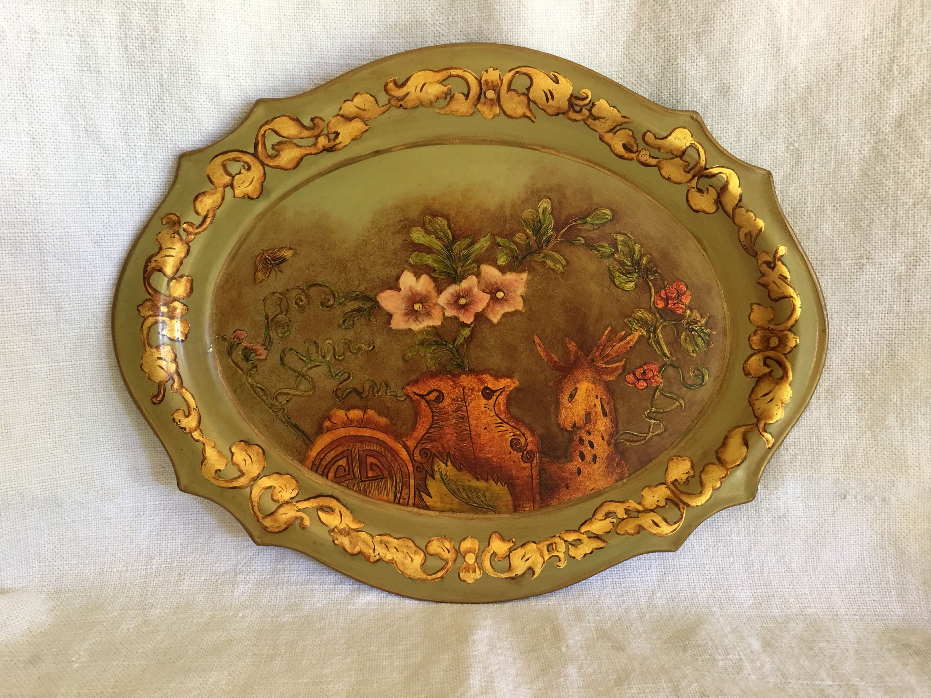 Beautiful hand painted dresser or jewelry tray that was done in 1962 by C.C.W, as indicated on the bottom. It is embellished with gold paint and depicts flowers, a butterfly, a vase and a deer. It has a beautiful cottage chic look to it and would compliment your decor nicely. It measures 8 wide,