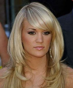 Carrie Underwood's sideswept bangs, side part, and layered curls that frame her face. #blonde #SquareFaceHairstyle