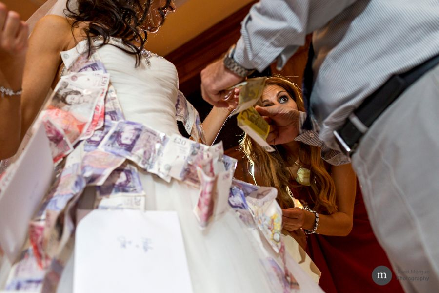 maid of honour pins money to bride's dress during greek money dance