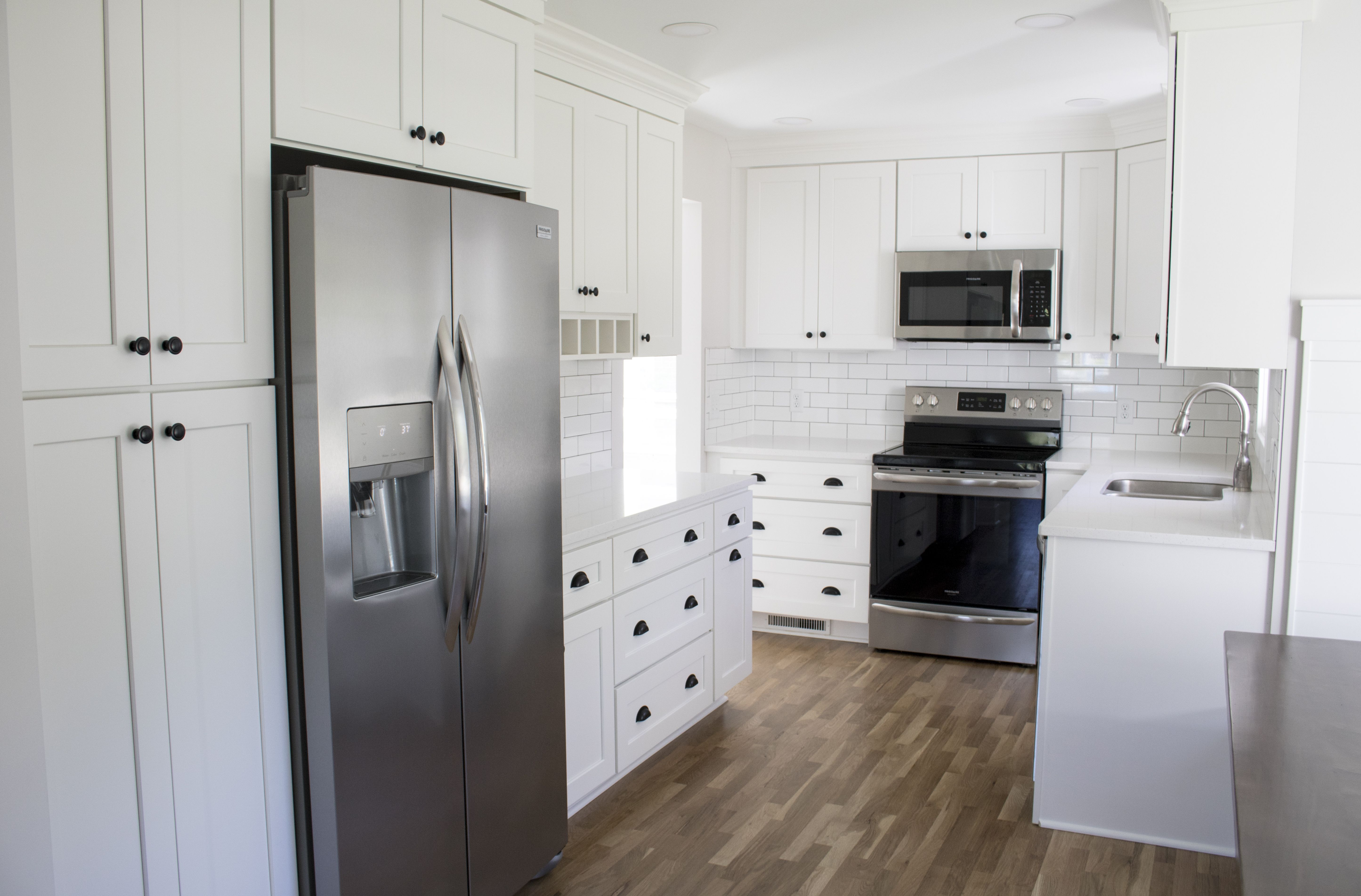 this is a timeless kitchen due to the all white cabinetry wood flooring black hardware on kitchen cabinets vertical lines id=40555