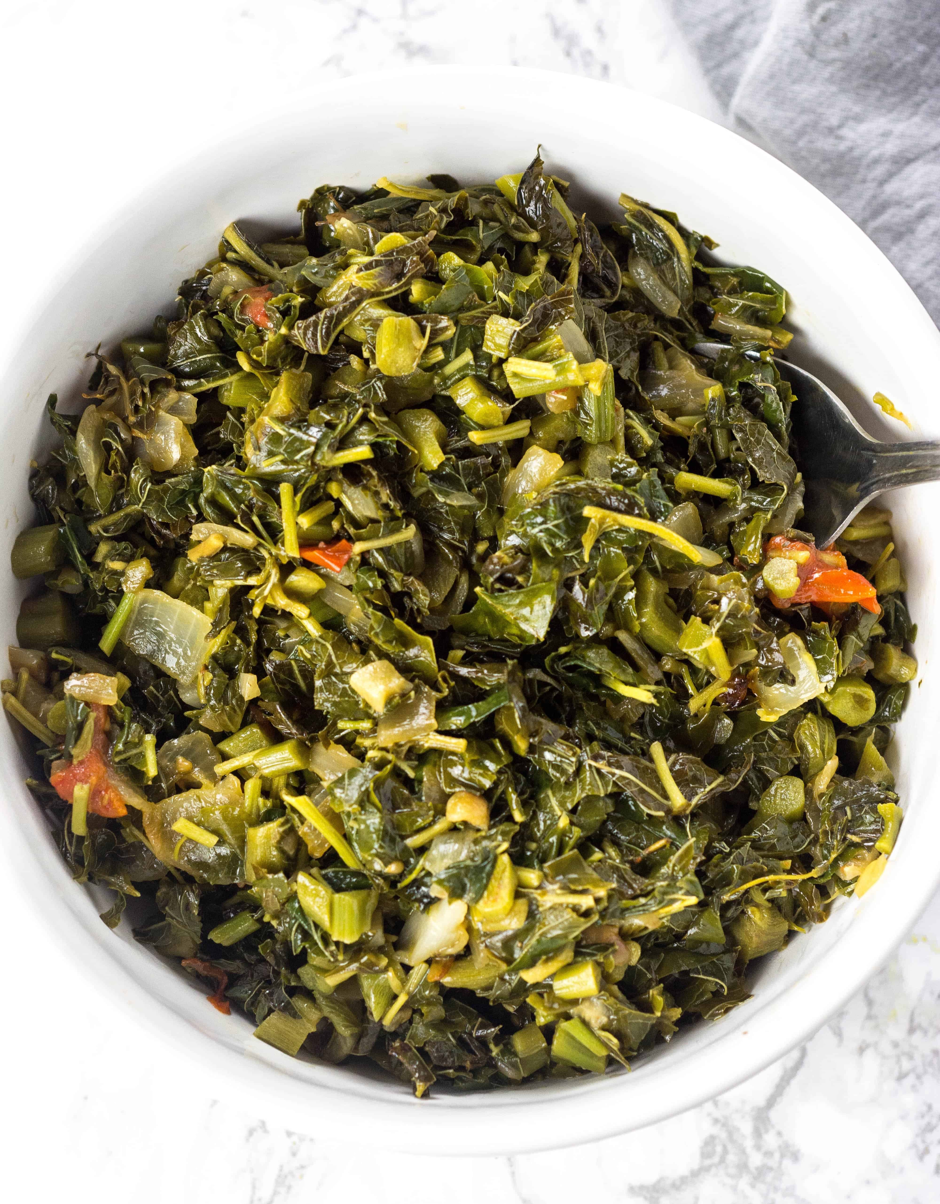 overhead photo of cooked jamaican callaloo in a white bowl