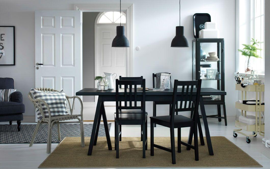 Zona pranzo con tavolo e sedie neri carrello beige e vetrina