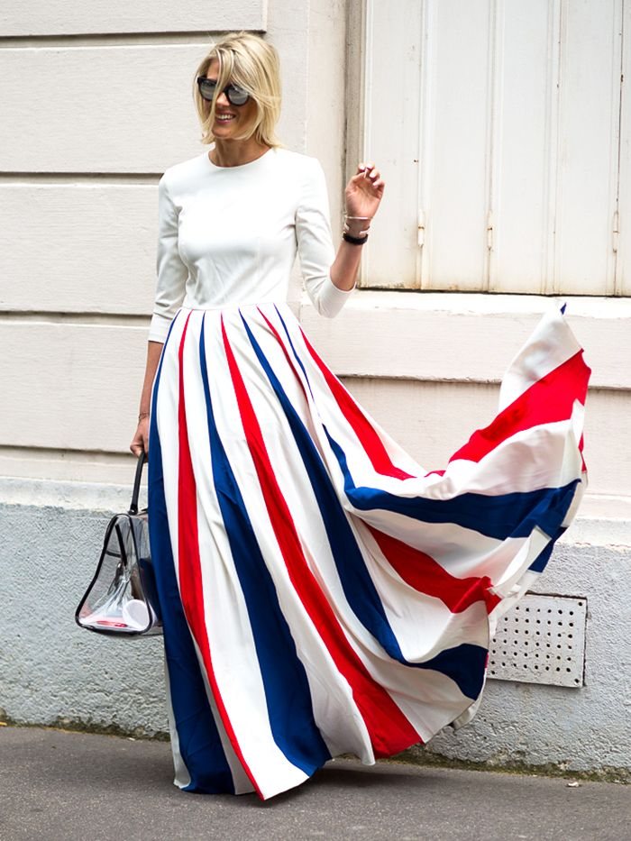 A white quarter sleeve top is tucked into a red, white, and blue striped maxi skirt