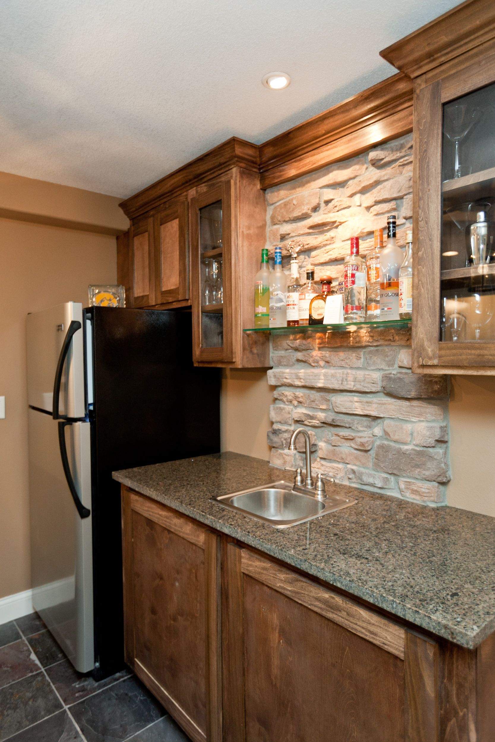 Wet Bar With Stone Column And Glass Shelves Basement
