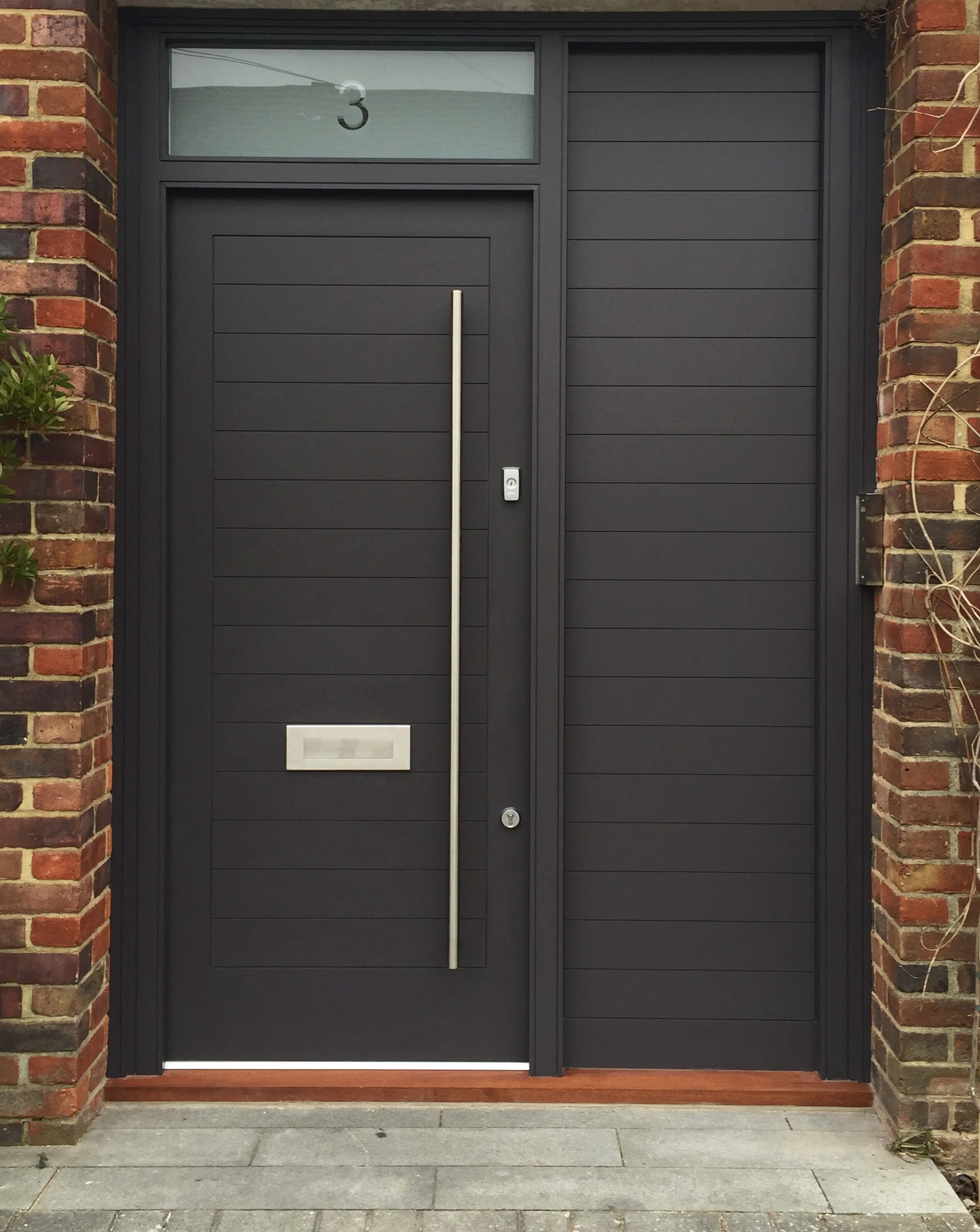 Stylish Front Door With A Bright Modern Finish And Brass Door