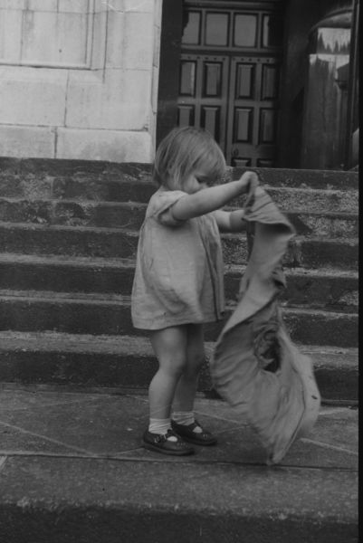 Little girl with a sack on the steps of a house in the East End of London, November 1954 (photo courtesy Henry Grant)