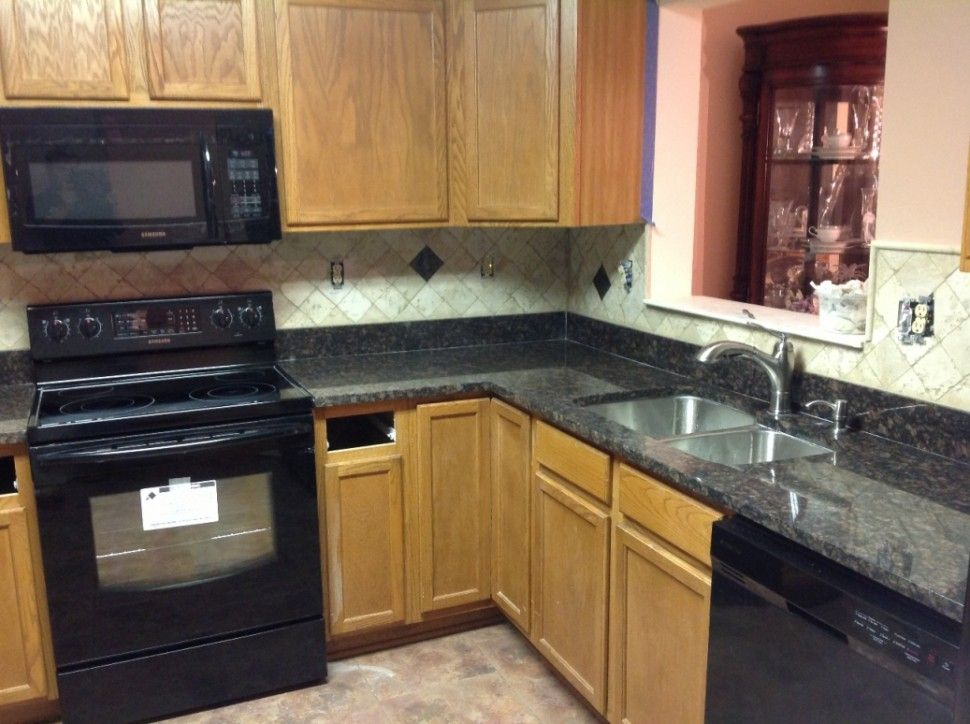 Kitchen quartz countertops with oak cabinets black for Kitchen cabinet countertop ideas