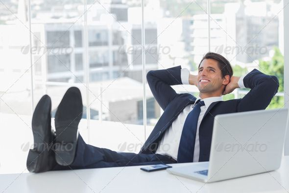 Successful Businessman In His Office Relaxing With His Feet On His