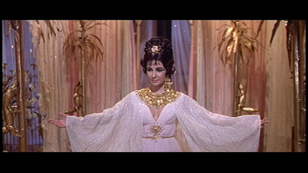 Elizabeth Taylor Cleopatra Cape | Cleopatra - Elizabeth Taylor wearing a white low-cut dress with ...