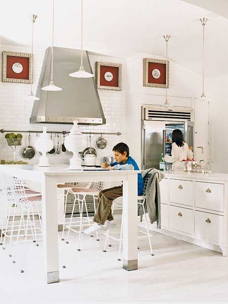 An all white kitchen gets all decked out in metallic accents, from the foot caps on the island to the hanging lights to the vent hood. A framed set of plates signed by The Beatles is the only adornment on the wall, matted on red and hung high above the cooking area. (Photo: Jeremy Samuelson)