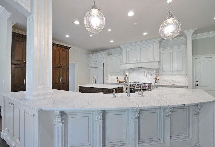 Elegant A Curved Kitchen Island With Extensive Millwork Honed