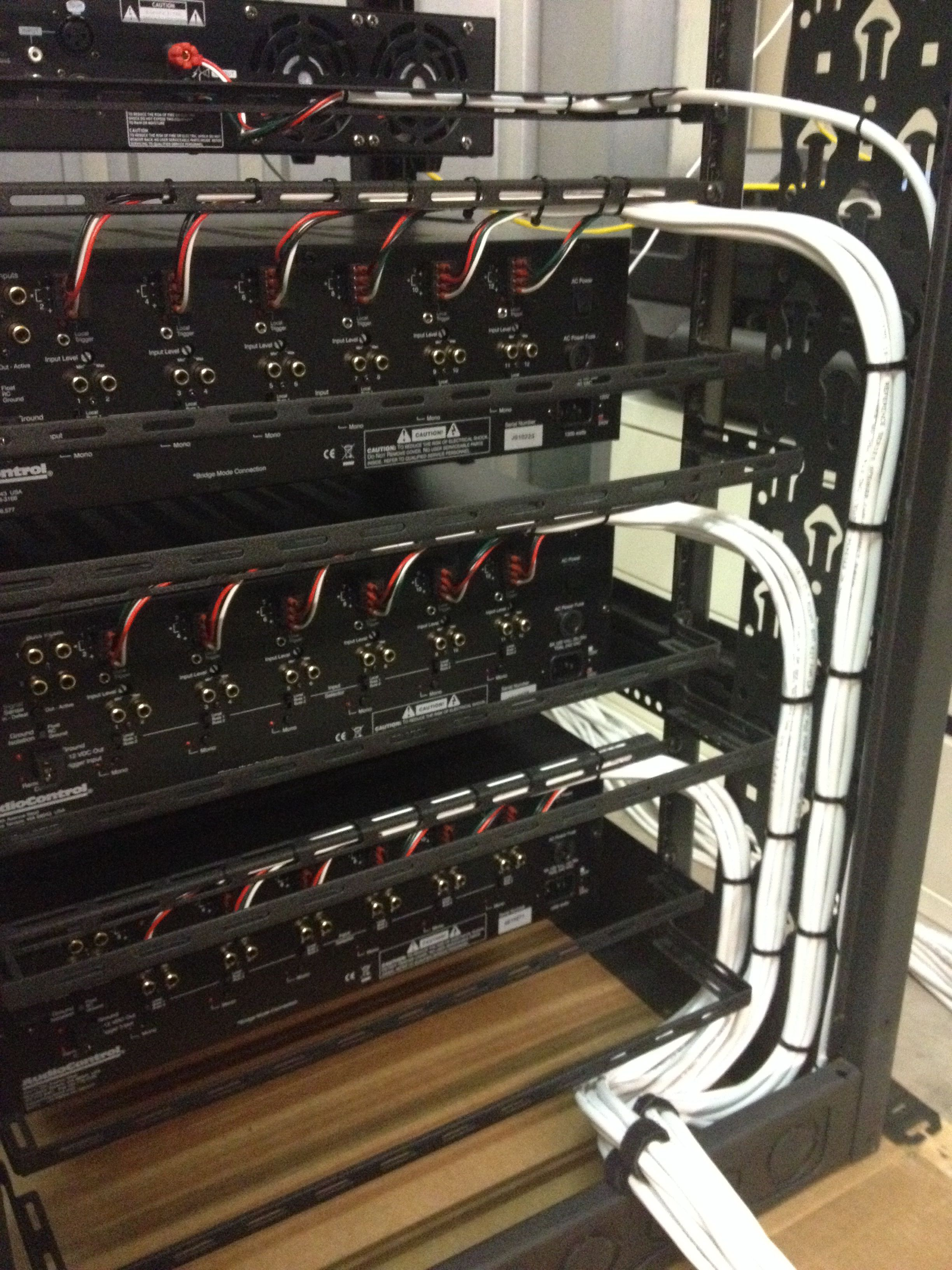hight resolution of rear view of equipment rack housing audio distribution system showing speaker cabling installation