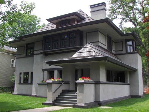 heavy window wills, front porch pointed roof, dark trim chimmney and corner features, wide roof overhang    Frank Loyd Wright house in shades of grey