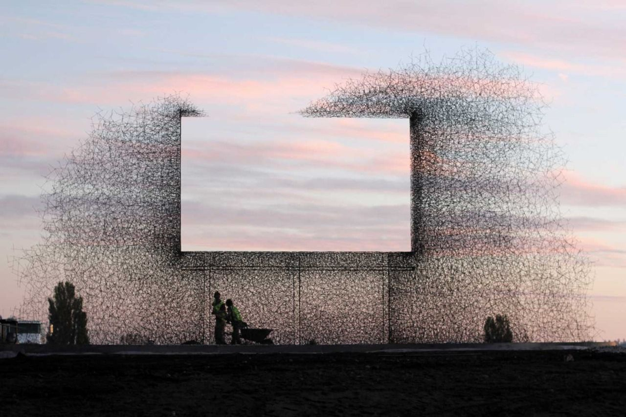 """Non-sign II is an installation by seattle based art collective Lead Pencil Studio located at the Canada-US border near Vancouver. The sculpture is made from small stainless steel rods that are assembled together to create the negative space of a billboard."""