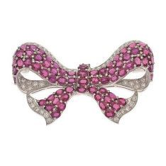 A ruby and diamond brooch, the stylised bow set with oval cut rubies totalling 23.73cts, within a border of round brilliant cut diamonds, totalling 2.70cts, in 18ct white gold