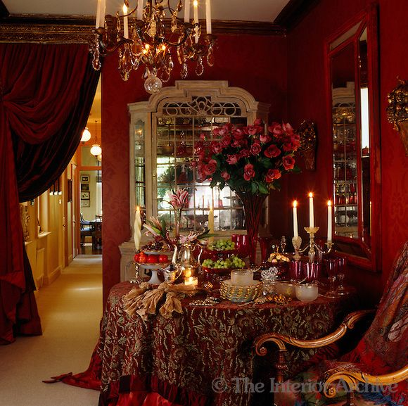 The use of sumptuous textiles such as the velvet curtains and tablecloth add to the drama of this opulent dining room - Stephanie Hoppen design