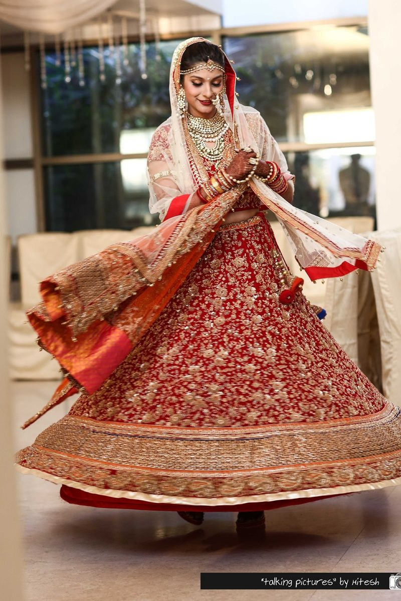 Twirling brides are our favourite! The bride enjoying her moment in her beautiful red wedding lehenga embellished with floral gold sequinned motifs and double drape dupatta.