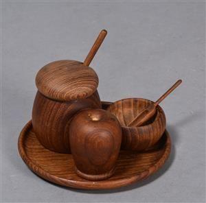 Kay Bojesen(1886-1958). Plat-de-menage af teaktræ, det lille fad m/ Kay Bojesen klister mrk., resten ustemplede, bestående af fad Ø 14,5 cm., peberbøsse H. 6 cm., sennepskrukke m/ glasindsats & spade H. 7,5 cm samt saltkar m/ ske Ø 5 cm. Fremstår m/ brugsspor. (4)