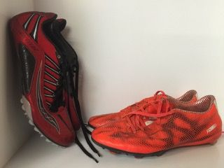 LOT INCLUDES TWO PAIR OF CLEATS - RED AND BLACK SPITFIRE SAUCONY RACING CLEATS IN A SIZE 12 AND ADIDAS NEON ORANGE AND WHITE SIZE 11 CLEATS. BOTH IN USED CONDITION.