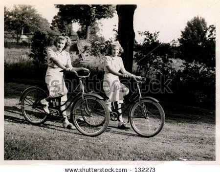 La foto de la ventaja de hermanas gemelas en bicicletas. Hacia 1930
