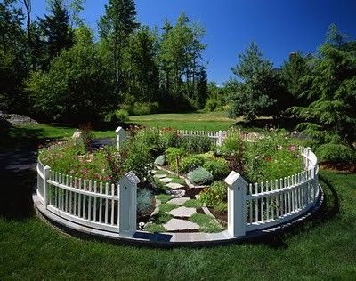 I love this idea - circular garden with picket fence, walkway and bird  houses atop