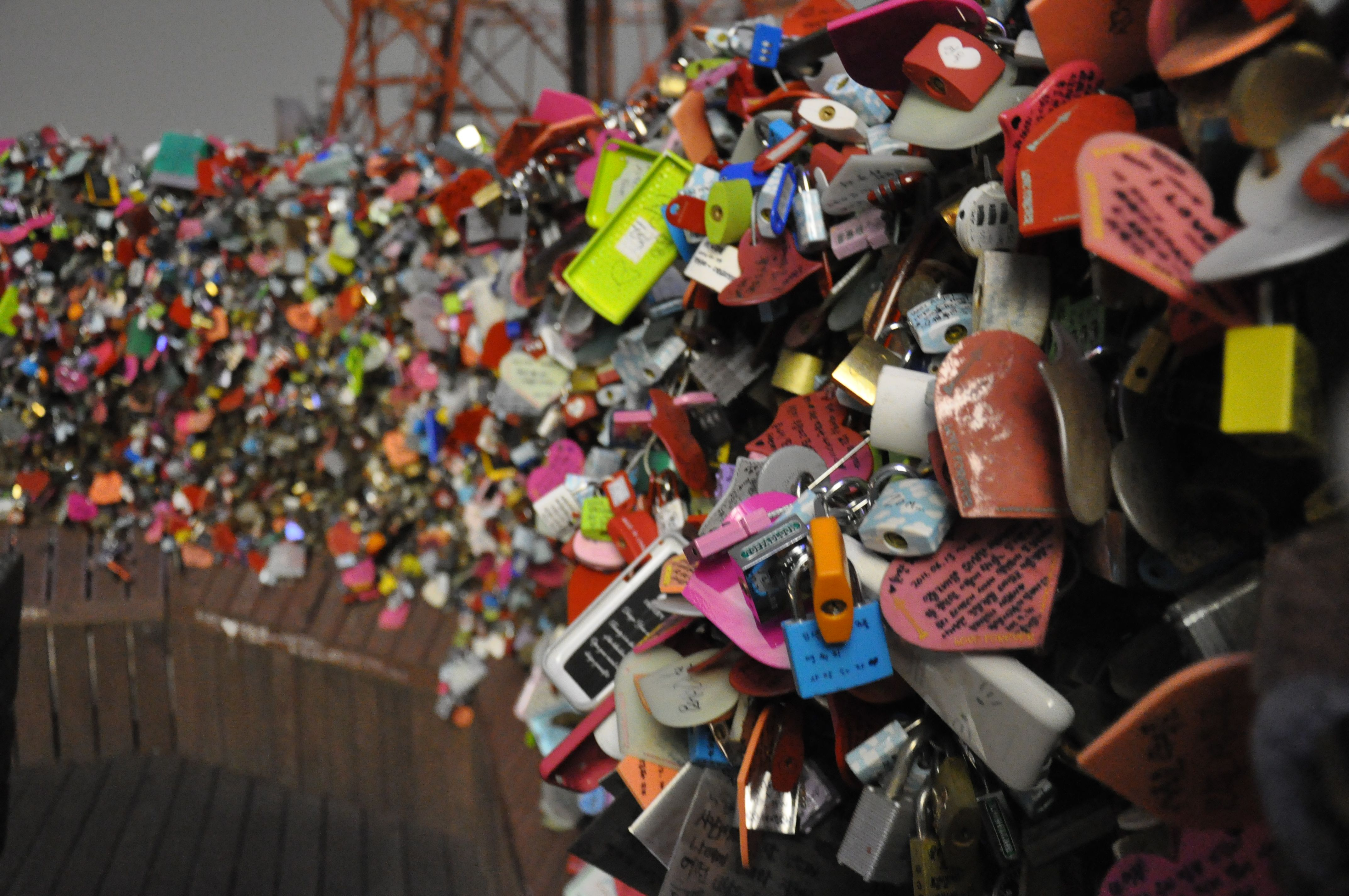 Namsan Tower  is a place filled with thousands and thousands of locks. Each belongs to a couple, accompanied with a message of their love. It is said that if a couple secures their lock on the rails of the tower and then tosses they key far down below – they will be together forever.