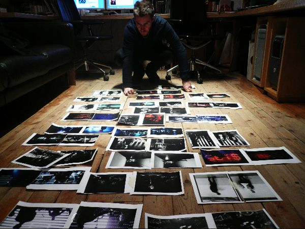 Photo of 3D inspecting the artwork and photography to be used for the Heligoland album.