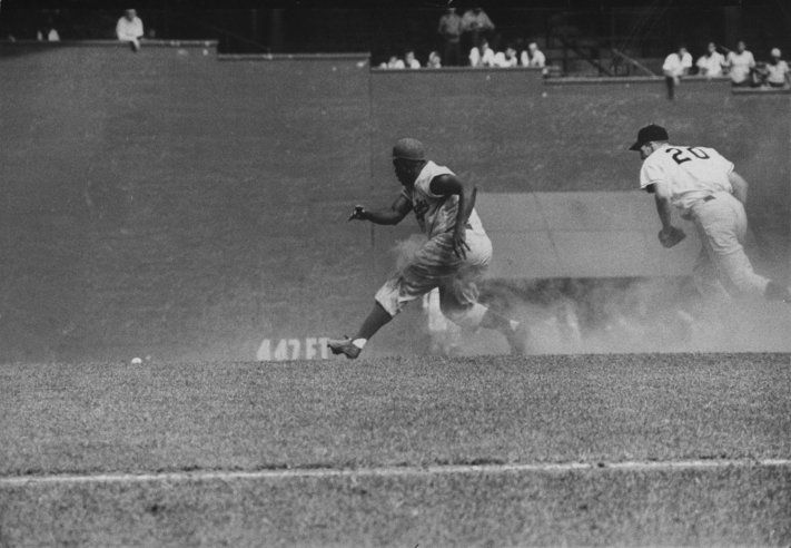 Caption from LIFE. Aging but still aggressive, Jackie Robinson bluffs for third after stealing second.