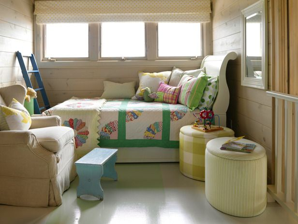 Cheerful prints and natural lighting provoke a carefree feel in the kids' loft. The twin bed includes a trundle bed to maximize sleeping capacity without taking up space. The mismatched quilts fulfill the cottage look that fits with the rest of the house.  Design by Sarah Richardson