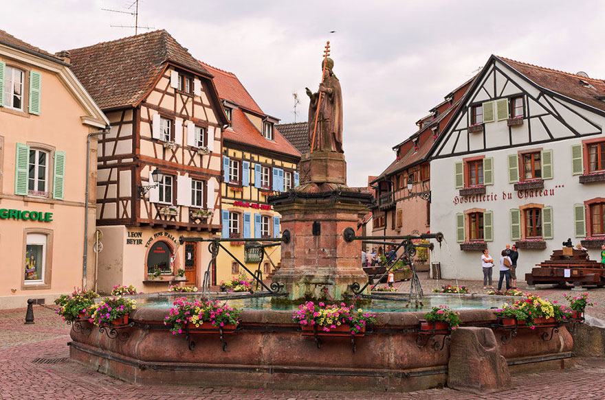 This small village square in Beauty And The Beast fairytale was inspired by Alsace, a picturesque region in North-West France that, throughout most of Europe's history, was politically German. As such, it has a blend of these two cultures, which can be found in the names of various locations and especially in the region's beautiful pastoral architecture.