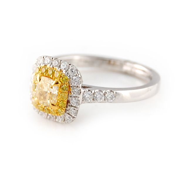 Fancy Yellow Cushion Cut Double Halo Diamond Ring! You will love the fabulous fashion and sleek styling of this gorgeous diamond ring! Center diamond is a .63 carat fancy yellow cushion cut, accented by a single halo of vivid fancy yellow round brilliants. Another halo of round brilliant diamonds surrounds the center with diamond accents in the band as well, in 14 karat white and yellow gold. 1.20 ctw