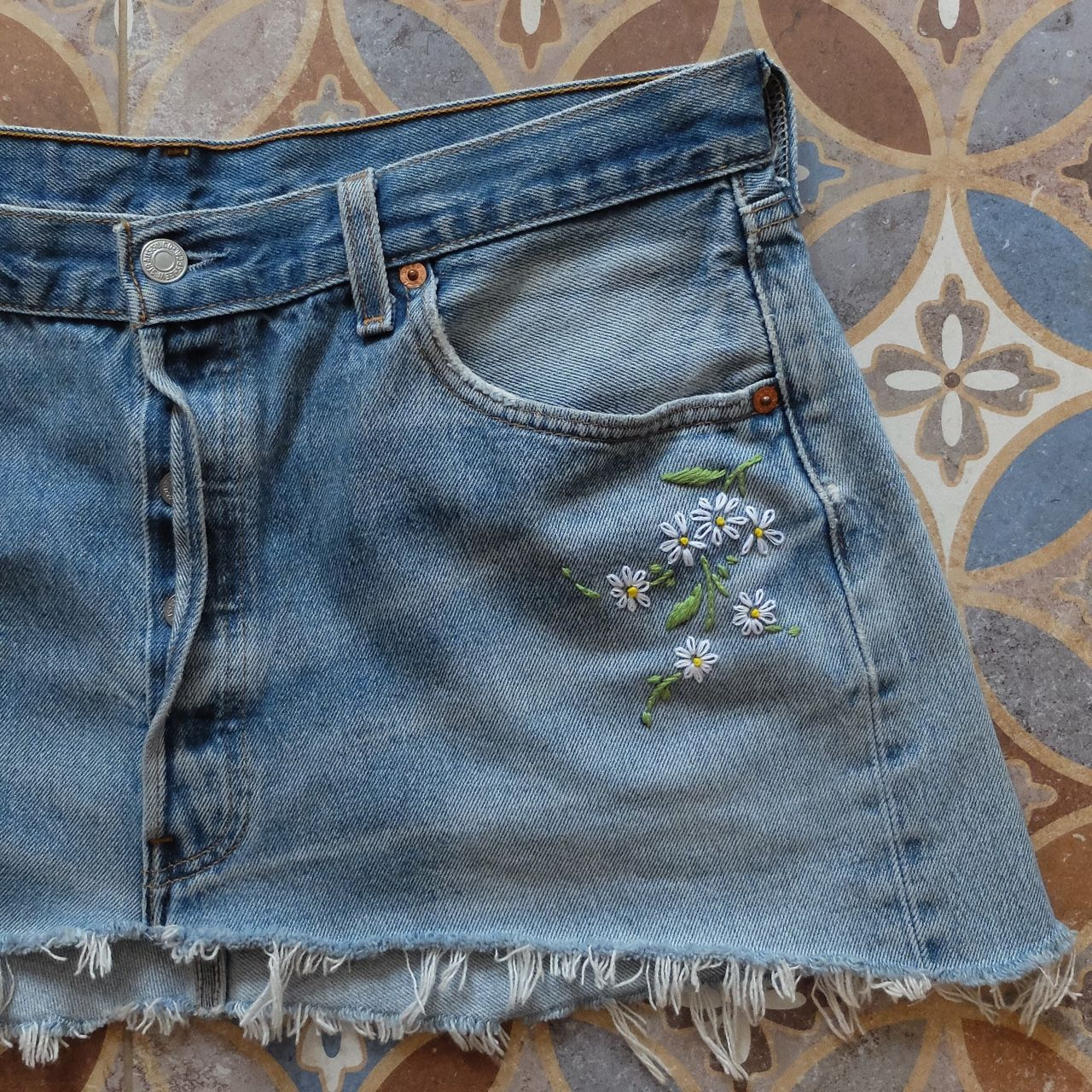 VINTAGE REWORKED Hand Embroidered Levis Jean Skirt. Stunning summer skirt reworked, restitched and recycled...by me! Super cute hand embroidered daisies below the front pocket and on the back below the waist band. Label reads Waist 34 - around a UK size 14-16 but please check measurements carefully. Gorgeous distressed denim in a stone wash blue, hand stitched with white and yellow daisy flowers. Completely one of a kind and unique! #reworked #restitched #recycled #handembroidery…