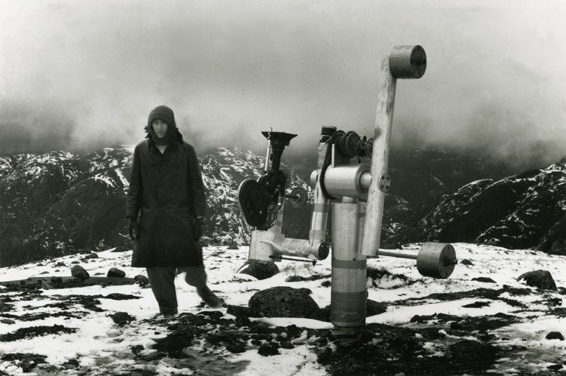 "Michael Snow with the machine he and Pierre Abeloos designed to film ""La Région Centrale."" The photo was taken by Joyce Wieland in October 1969 on the fifth and final day of the crew's presence on the mountaintop in northern Quebec where the film was shot."