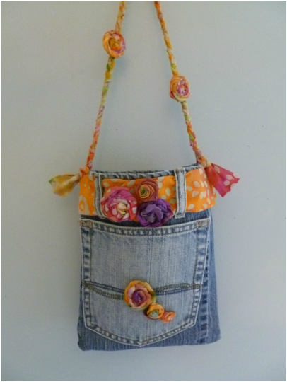 Upcycled blue jean handbag - made out of salvaged pieces of old jeans, leftover fabric, and embellished with handmade fabric rosettes.  Small size makes it fun for any age. #blue