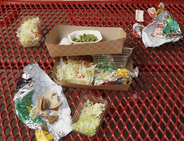 Vegetables left over by students sit on cafeteria trays at the Roosevelt High School in Los Angeles. Americans blame too much screen time and cheap fast-food for fueling the nation's obesity epidemic.