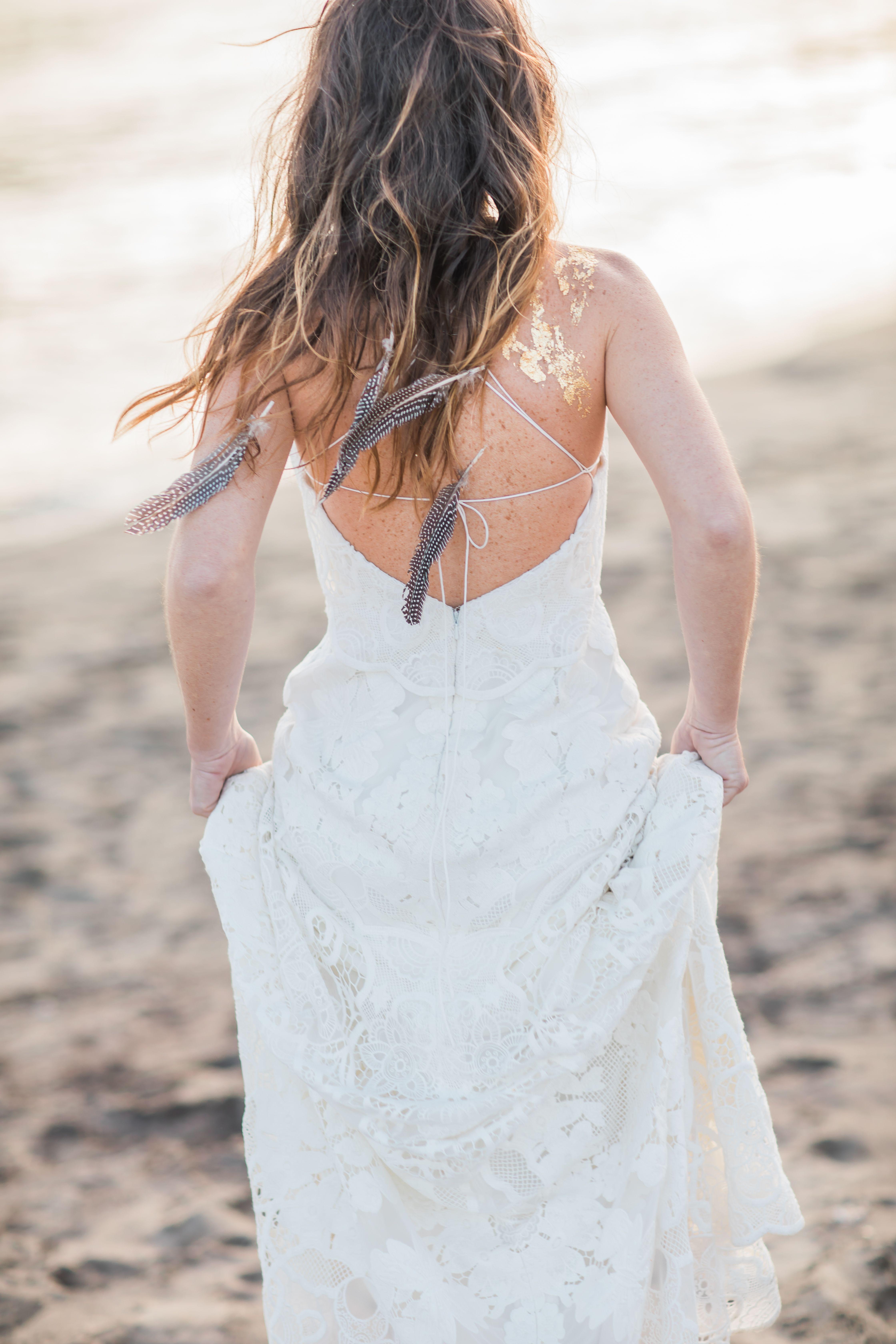 Hochzeit am Strand im Boho-Stil. Lockere Brautfrisur mit Federn und ...
