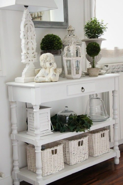 i love everything about this picture. i love how the console table is set up with everything on it (plants, lanterns, angel, baskets) and the mirror over it....