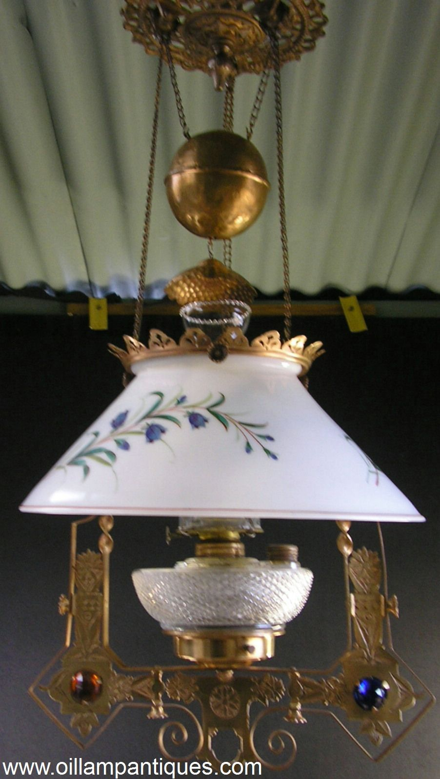 This smaller sized hanging oil lamp was often referred to as a kitchen lamp. Although less ornate than some of the bigger parlour hanging lamps, it is still very elegant and appealing. The hand painted slant sided shade is complimented nicely by the inset jewels and the ornately patterned frame.
