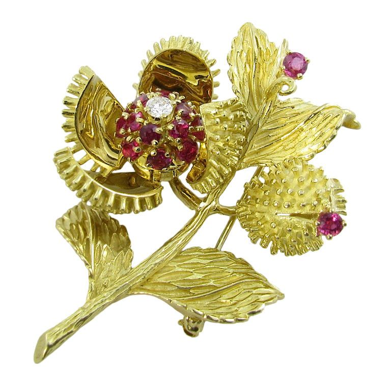 TIFFANY & CO. Ruby Diamond and Yellow Gold Brooch.  The brooch is a pod and leaf design with one pod that opens up to reveal a bud set with (14) fourteen rubies, and (1) one diamond. The brooch is set with (2) two additional rubies on the leaves. The brooch measures approximately 2 inches high and 1 1/2 inches wide. Approximate gross weight 29.9 grams. Circa 1970s