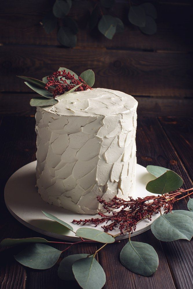 White cream cake decorated with green leaves of the eucalyptus tree on a wooden stand in a rustic style. Trends for wedding desserts, food design