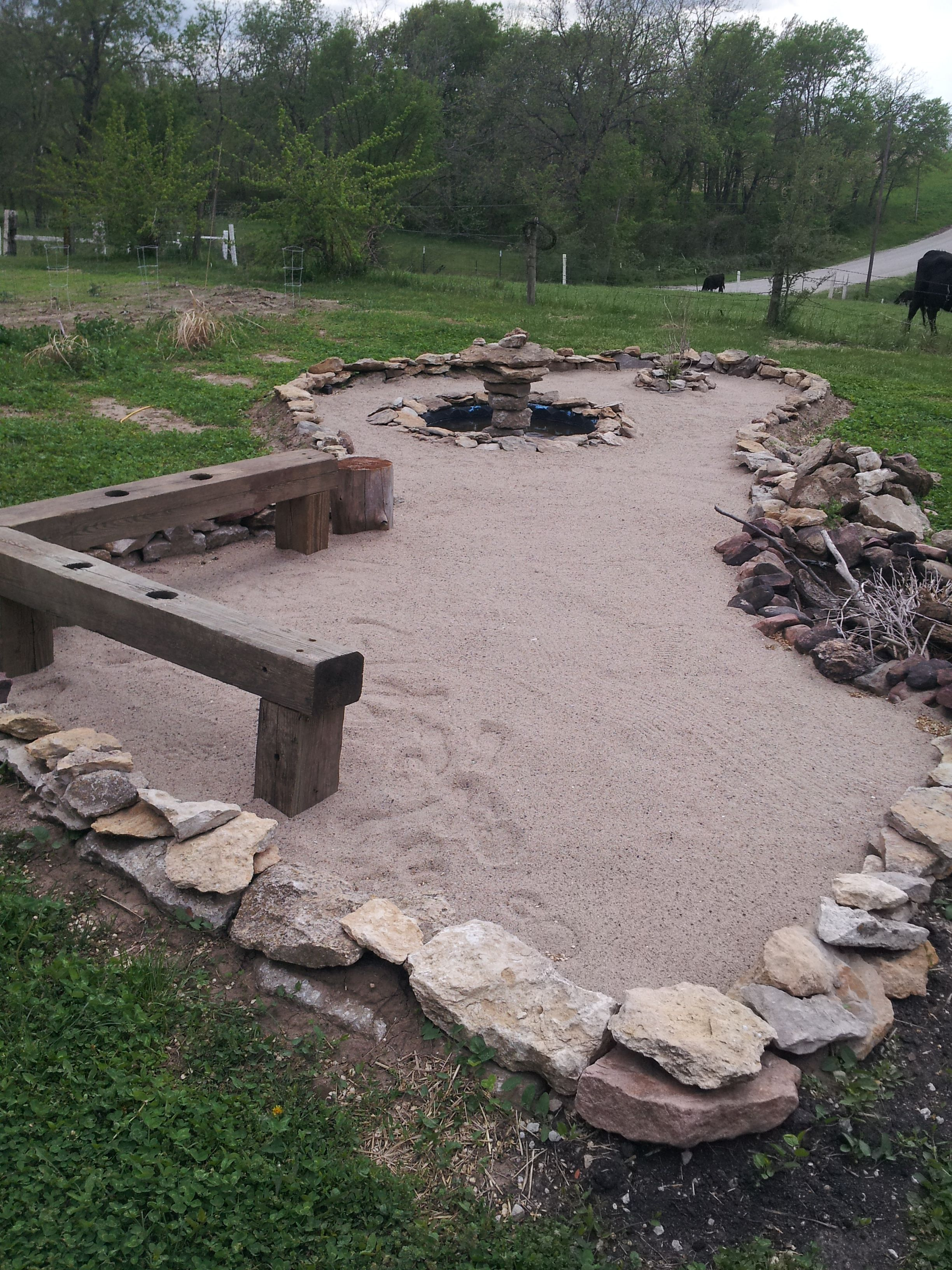 Sand Firepit, Rock Fountain, Cost for us $100 to build this. Rock -Free, We had the timbers, used a plastic swimming pool that we had & Fish pump that we had but i had paid $1 for it (Garage Sale), used tarps for liner & PAID for Sand from local Quarry. Right Side Corner Fire pit, in the center takes up a lot of space. This is still a work in progress, adding a Rock Grill & Pergola.