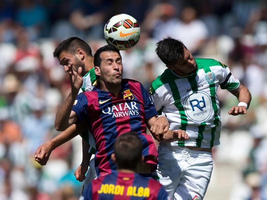 Sergio Busquets Burgos, del Barça, lucha con Luso Delgado y Borja García, del Córdoba, por un balón.