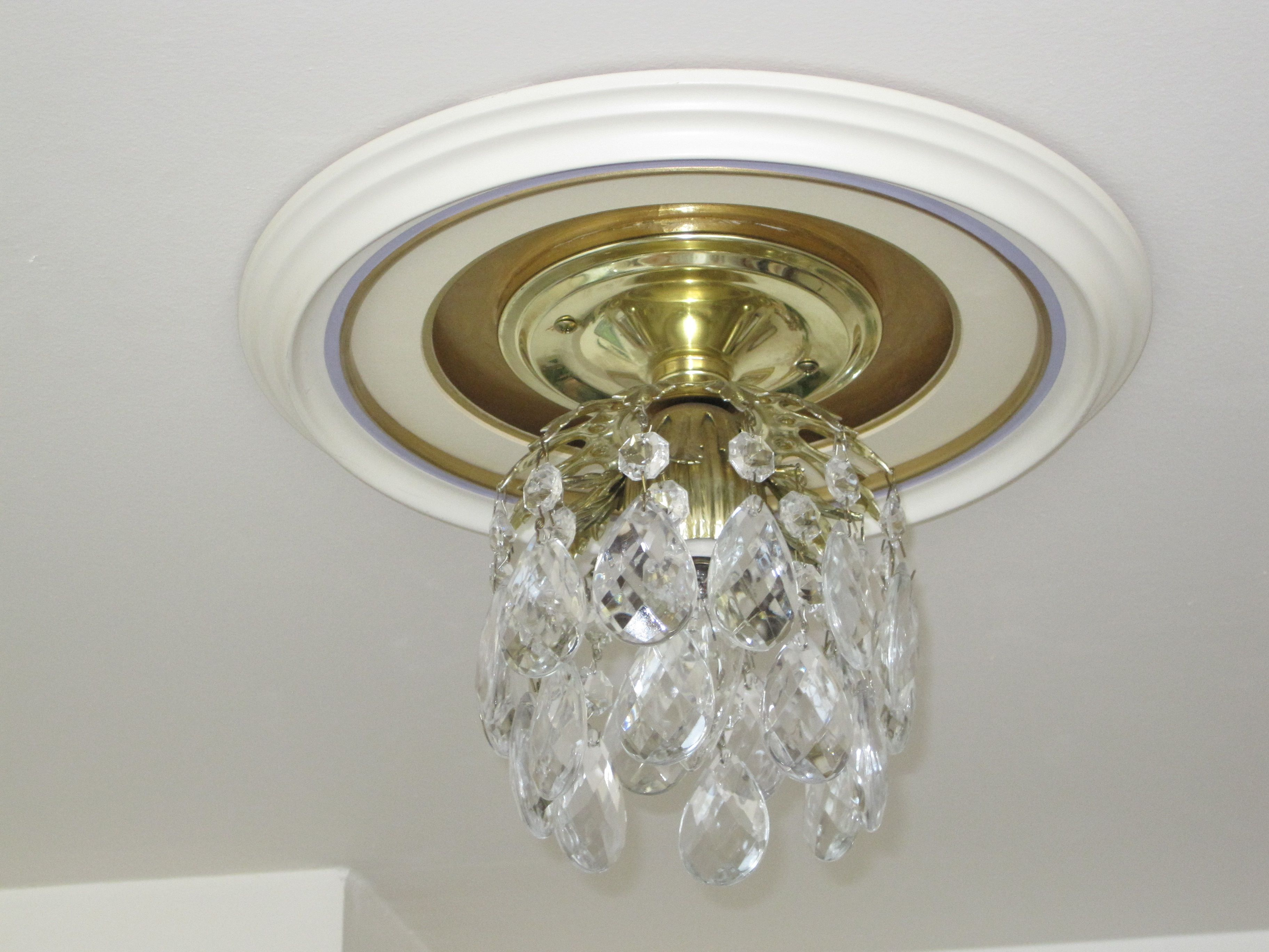 Using a picture frame as a medallion for a ceiling light fixture.