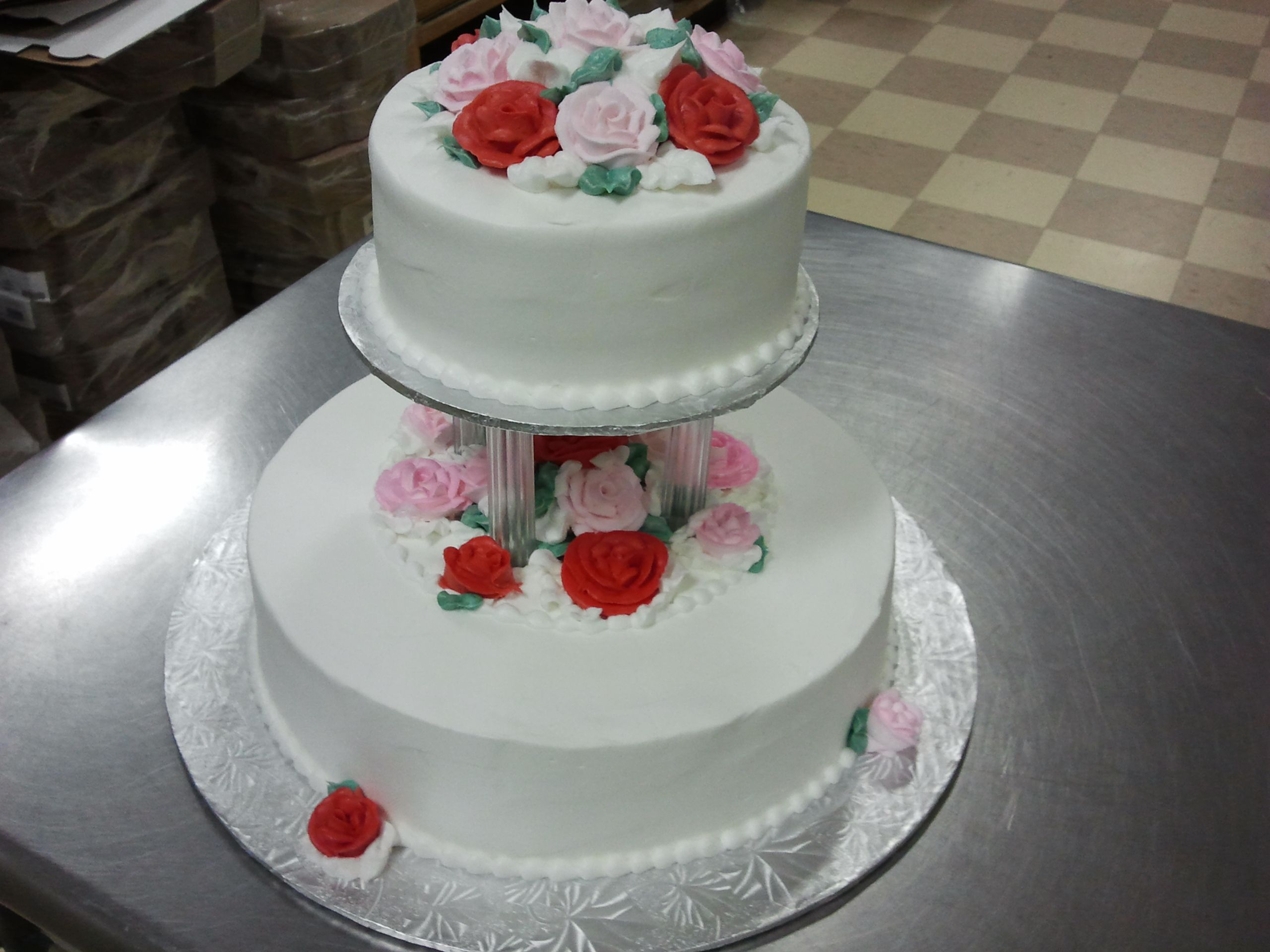 Top tier separated. Smooth buttercream with pale pink and red roses.