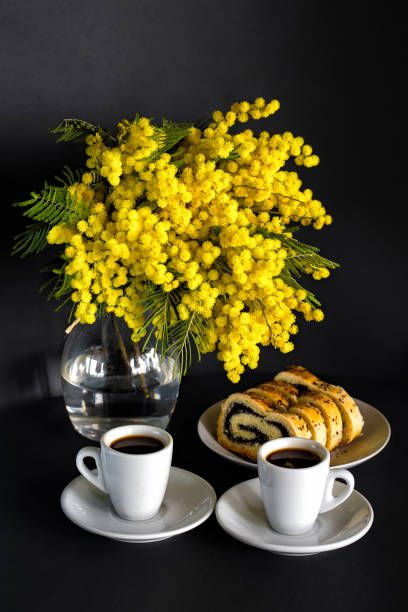 vase with mimosa two cups of coffee and poppy seed strudel on a black