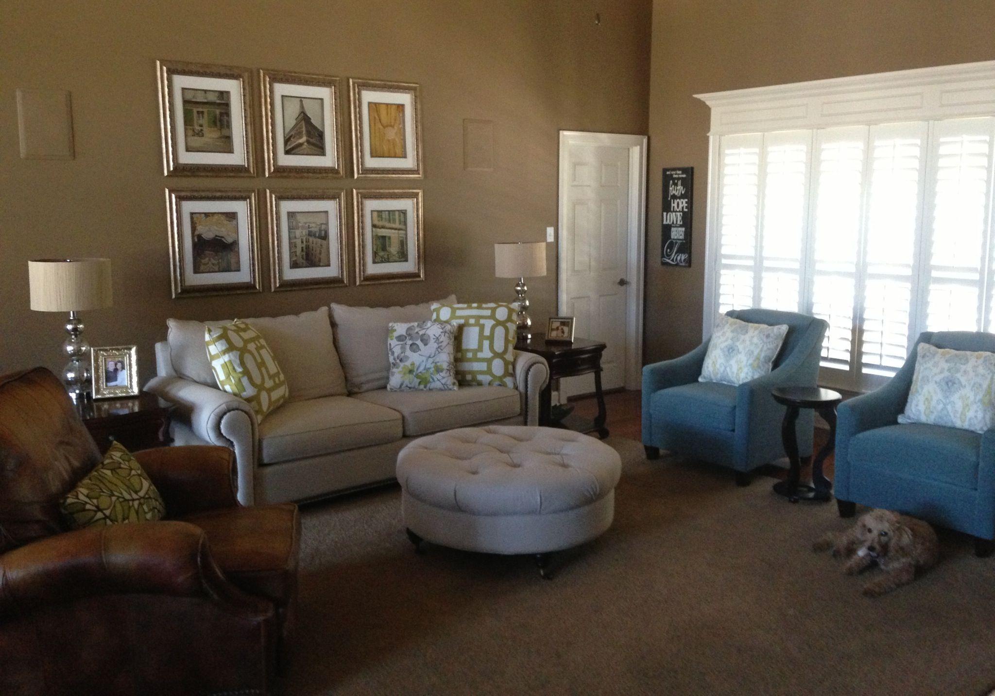 Gallery.  Blue chairs.  Green geometric pillows.  Linen sofa.