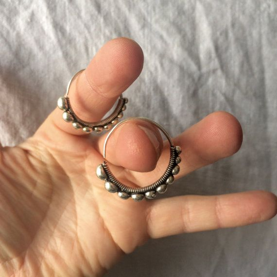 These vintage earrings come from the Miao tribe of China. Continuous hoops of graduated silver bubbles. Miao Hmong silver jewelry is distinctive for its design, style and craftsmanship.   For more great tribal and mineral earrings check out the earring section of our shop: https://www.etsy.com/shop/aadyabazaar?ref=hdr_shop_menu&section_id=11558503  A portion of each sale goes to support women's craft collectives, microfinance projects in India, Africa and Afg...