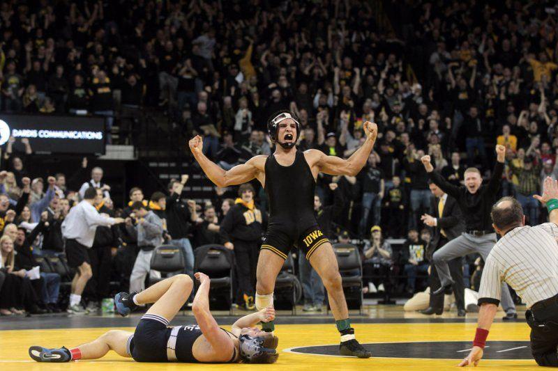 Iowa's Tony Ramos celebrates after pinning Penn State's