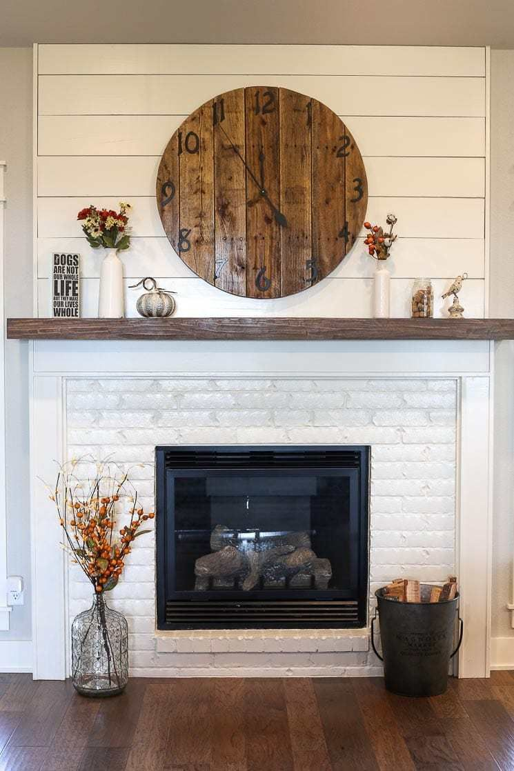 A picture of a fireplace with painted white brick and shiplap. #whitebrickfireplace